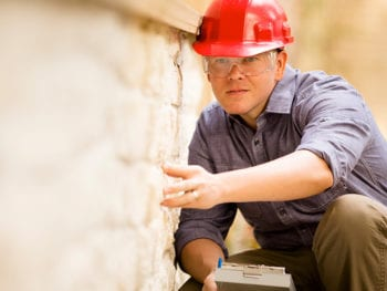 Man wearing red hard hat and safety glasses inspecting brick wall.