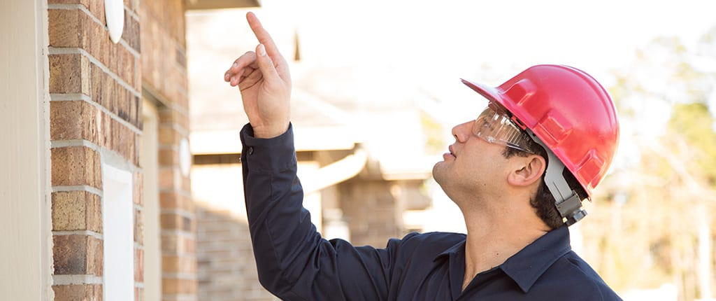 Man wearing red hard hat pointing.