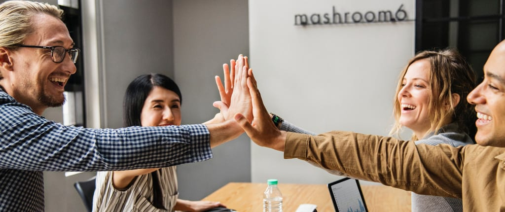 Coworkers around a table high-fiving