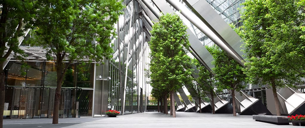 The front entrance of a office building complex surrounded by trees.